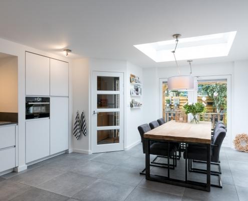 woonkamer met dakraam en lichte witte keuken